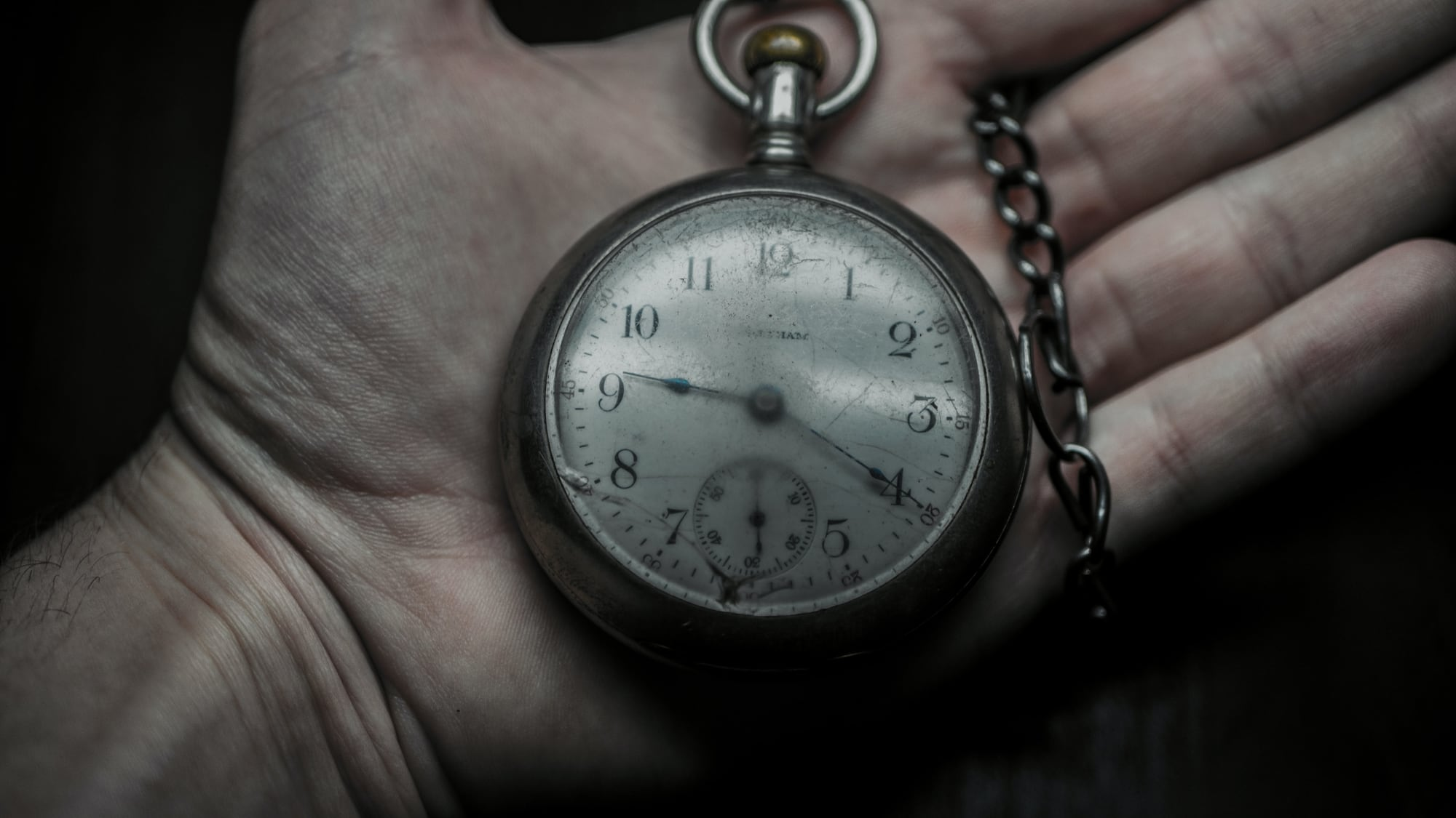 Hand holding old pocket watch.